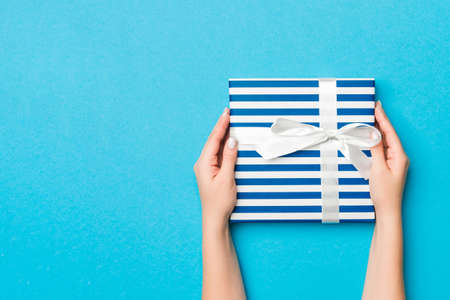 Woman arms holding gift box with colored ribbon on blue table background, top view and copy space for you design. 版權商用圖片