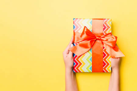 Woman arms holding gift box with colored ribbon on yellow table background, top view and copy space for you design. 版權商用圖片