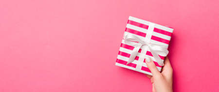 Girl Hands holding craft paper gift box with as a present for Christmas or other holiday on pink background, top view with copy sppace. 版權商用圖片