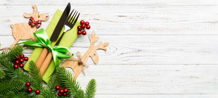 Banner top view of holiday objects on wooden background. Utensils tied up with ribbon on napkin. Christmas decorations and reindeer with copy space. New year dinner concept.