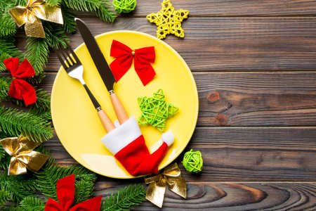 Top view of fork, knife and plate surrounded with fir tree and Christmas decoratoins on wooden background. New Year Eve and holiday dinner concept. 版權商用圖片
