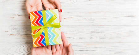 Top view of giving and receiving a present on wooden background. A man and a woman holding gift in hands. Festive concept with copy space.