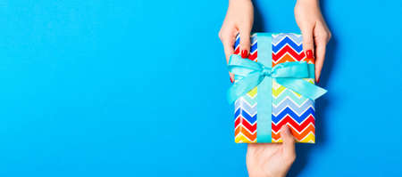 Top view of holding a gift in female and male hands on colorful background. Woman and man give and receive a present. Close up of time for holiday concept.