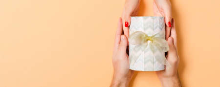 Top view of a man and a woman giving and receiving gift for a holiday on colorful background. Love and relationship concept with copy space.