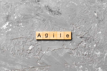 Agile word written on wood block. Agile text on cement table for your desing, concept. 版權商用圖片