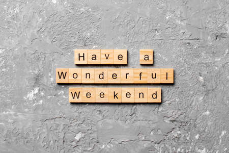Have a wonderful weekend word written on wood block. Have a wonderful weekend text on cement table for your desing, Top view concept. 版權商用圖片