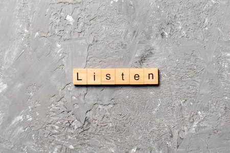 listen word written on wood block. listen text on table, concept.