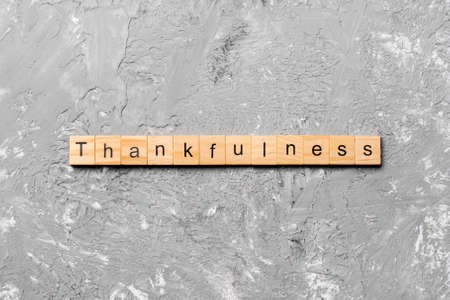 Thankfulness word written on wood block. Thankfulness text on cement table for your desing, concept. 版權商用圖片