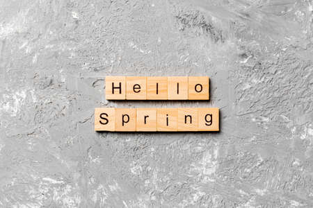 hello Spring word written on wood block. hello Spring text on cement table for your desing, concept. 版權商用圖片