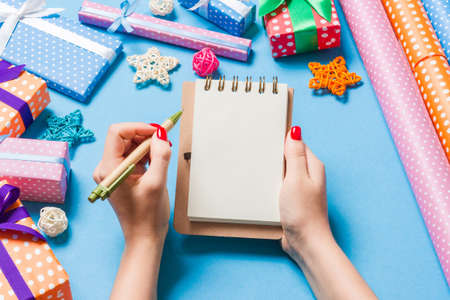 Top view of female hand making some notes in noteebok on blue background. New Year decorations and toys. Christmas time concept. 版權商用圖片
