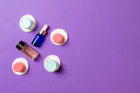 Set of travel size cosmetic bottles on colored background. Flat lay of cream jars. Top view of bodycare style concept. 版權商用圖片