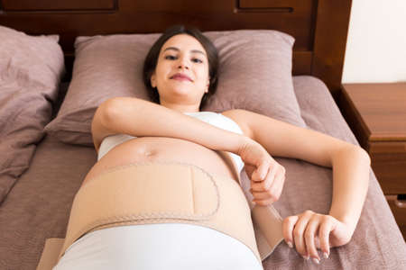 closeup pregnant woman dresses bandage on belly at home on bed. Orthopedic abdominal support belt.