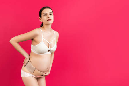 Portrait of supporting bandage against backache on pregnant woman in underwear at pink background with copy space. Mother is suffering from pain in the back. Orthopedic abdominal support belt concept.