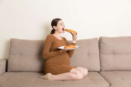 Pregnant woman sitting on the sofa is eating croissants from a plate at home. Unhealthy diet. Control your weight during pregnancy concept.