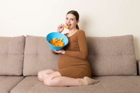 Pregnant woman sitting on the sofa enjoys eating potato chips from a bowl at home. Feeling hungry during pregnancy concept.