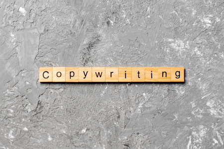 Copywriting word written on wood block. Copywriting text on cement table for your design, concept.