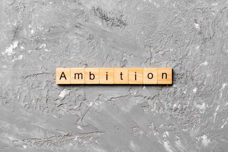 ambition word written on wood block. ambition text on cement table for your desing, concept. Archivio Fotografico