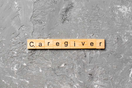 Caregiver word written on wood block. Caregiver text on table, concept.