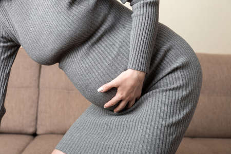 Pregnant Lady Having Massaging Lower belly Sitting On Sofa Indoor. Pregnancy Problems Concept. Maternity healthcare.