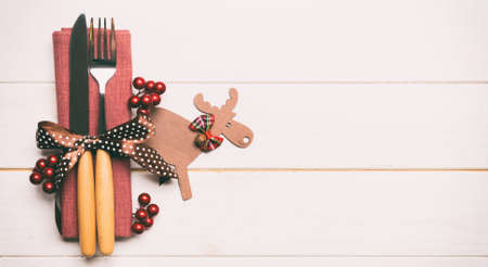 New year set of fork and knife on napkin. Banner Top view of christmas decorations and reindeer on wooden background. Holiday family dinner concept with empty space for your design.