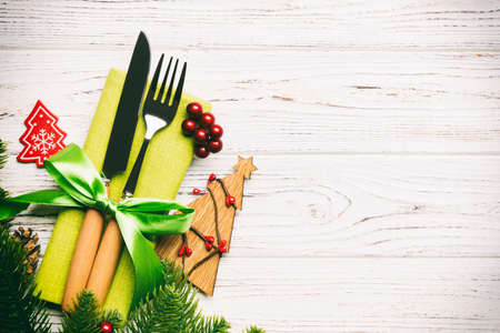 Top view of fork and knife on napkin with christmas decorations and new year tree on wooden background. Holiday and festive concept with copy space. Stok Fotoğraf