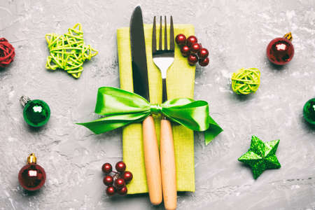 Top view of holiday set of fork and knife on cement background. Close up of Christmas decorations and toys. New Year Eve concept.