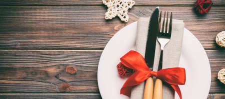 Holiday composition of Christmas dinner on wooden background. Top view of plate, utensil and festive decorations. New Year Advent concept with copy space. Stok Fotoğraf