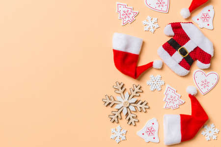 Top view of Christmas decorations and Santa hats on orange background. Happy holiday concept with copy space.