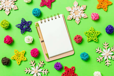 Top view of notebook. New Year decorations on green background. Festive stars and balls. Merry Christmas concept. Stok Fotoğraf