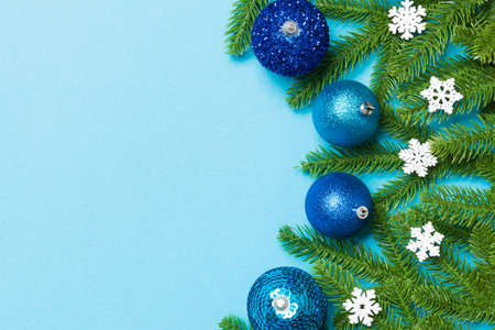 Christmas composition made of fir tree, balls and different decorations on colorful background. Top view of New Year Advent concept with empty space for your design.