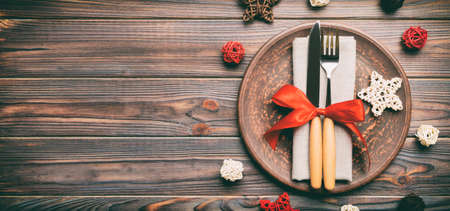Banner holiday composition of Christmas dinner on wooden background. Top view of plate, utensil and festive decorations. New Year Advent concept with copy space. Stok Fotoğraf