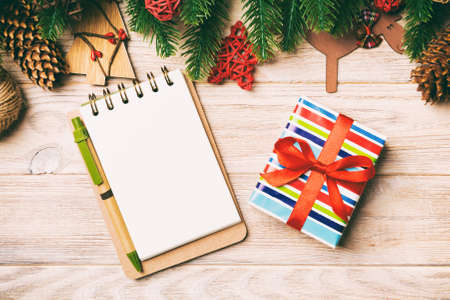 Top view of gift, notebook, Christmas toys, decorations and fir tree branches on wooden background. New Year holiday concept.