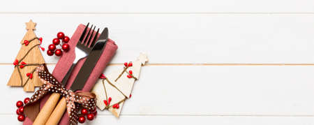 Banner top view of fork and knife tied up with ribbon on napkin on wooden background. Christmas decorations and New Year tree. Happy holiday concept with empty space for your design. Stok Fotoğraf