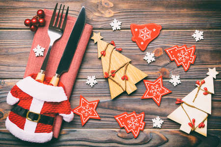 Top view of fork and knife tied up with ribbon on napkin on wooden background. Close up of christmas decorations and New Year tree. Happy holiday concept.