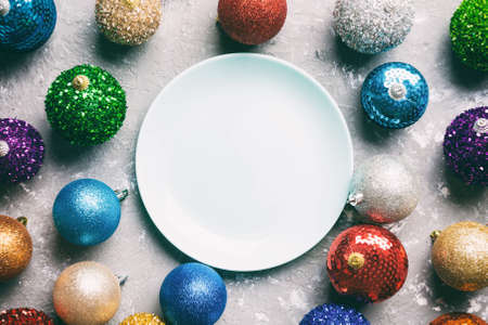 Top view of empty plate surrounded with colorful baubles on cement background. New Year decorations. Christmas Eve concept.