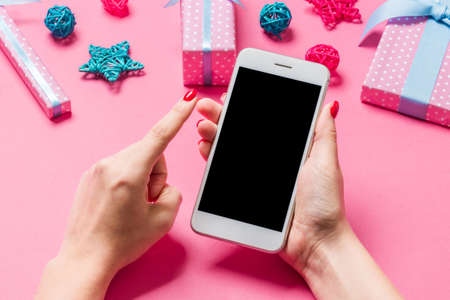 Top view of phone in female hand on festive pink background. Christmas decorations. New Year time holiday. Mockup. Stok Fotoğraf
