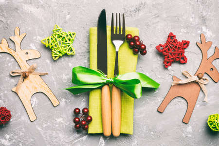 Top view of new year utensils on napkin with holiday decorations and reindeer on cement background. Close up of Christmas dinner concept.