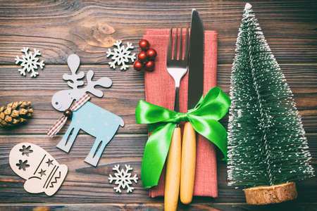 Top view of fork and knife tied up with ribbon on napkin on wooden background. Close up of christmas decorations and New Year tree. Happy holiday concept. Stok Fotoğraf