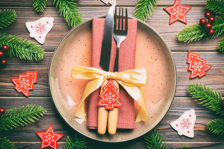 Top view of cutlery and plate on festive wooden background. New Year family dinner concept. Fir tree and Christmas decorations.