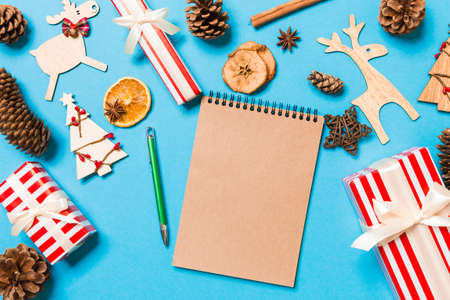 Top view of notebook on blue background made of Christmas decorations. New Year time concept.