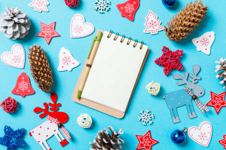 Top view of notebook surrounded with New Year toys and decorations on blue background. Christmas time concept.