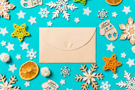 Top view of craft envelope on blue background with New Year toys and decorations. Christmas time concept. Stock fotó