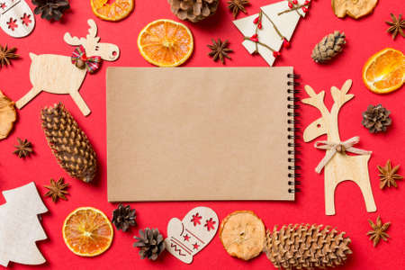 Top view of notebook, red background decorated with festive toys and Christmas symbols reindeers and New Year trees. Holiday concept. Stok Fotoğraf
