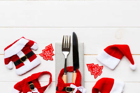 Festive set of fork and knife on wooden background. Top view of new year decorations and santa clothes and hat. Christmas concept with copy space.