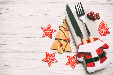 Top view of fork and knife tied up with ribbon on napkin on wooden background. Christmas decorations and New Year tree. Happy holiday concept with empty space for your design.