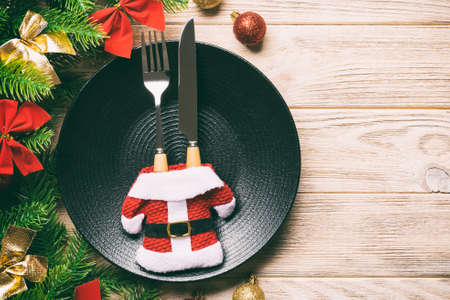 Top view of fork, knife and plate surrounded with fir tree and Christmas decoratoins on wooden background. New Year Eve and holiday dinner concept. Stok Fotoğraf