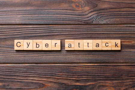 Cyber attack word written on wood block. Cyber attack text on cement table for your desing, concept.
