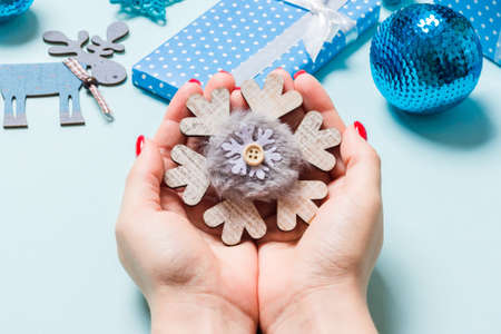 Top view of snowflake in female hands on blue background. Christmas decorations. New Year holiday concept.