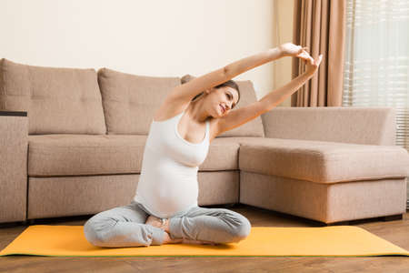 Pregnancy Yoga and Fitness concept at coronavirus time. Pregnant woman meditates indoor in yoga pose. Woman enjoying in meditation.