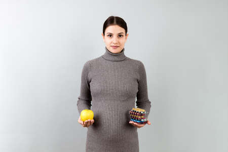 pregnant woman making a choice between an apple and a pile of pills at colorful background with copy space. Taking vitamins during pregnancy concept.